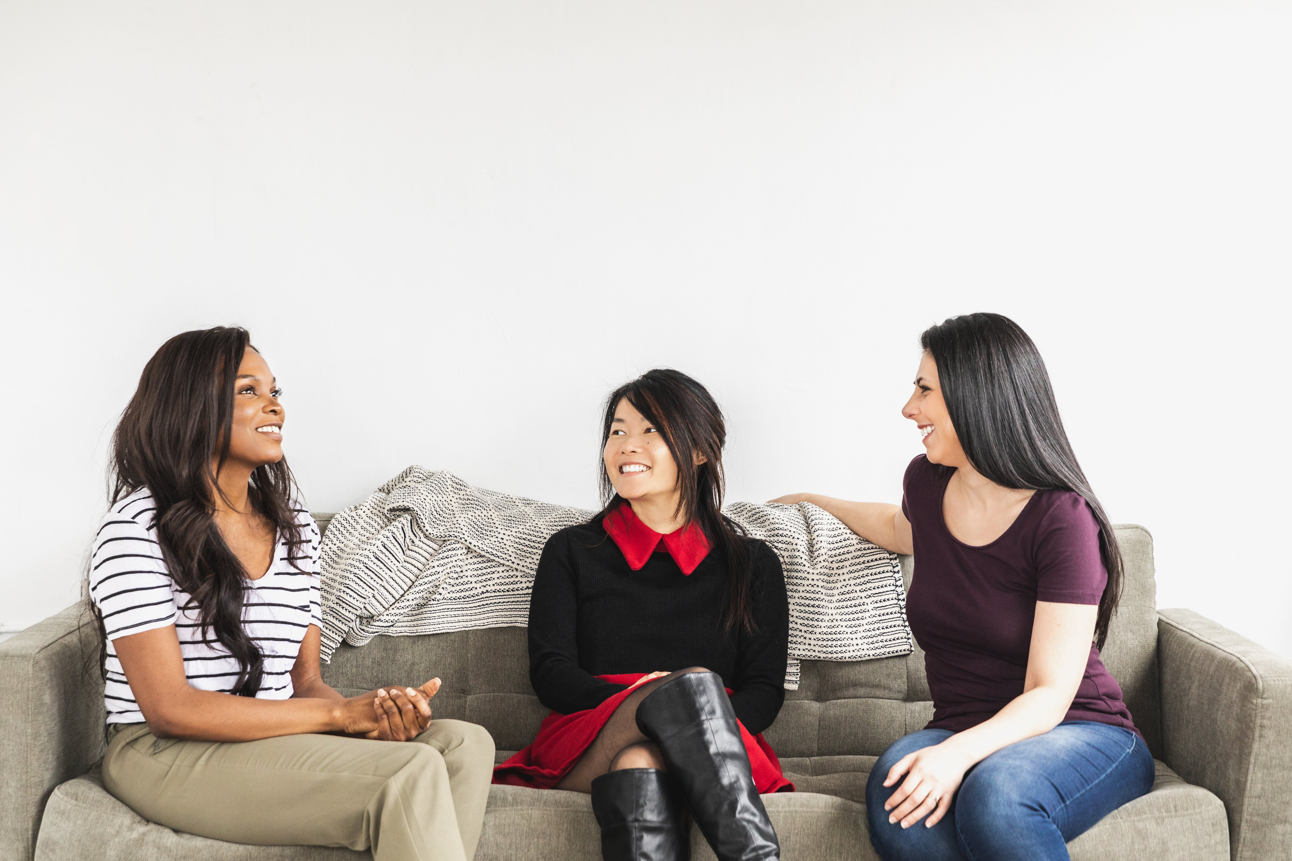 three women speaking to one another on a gray sofa