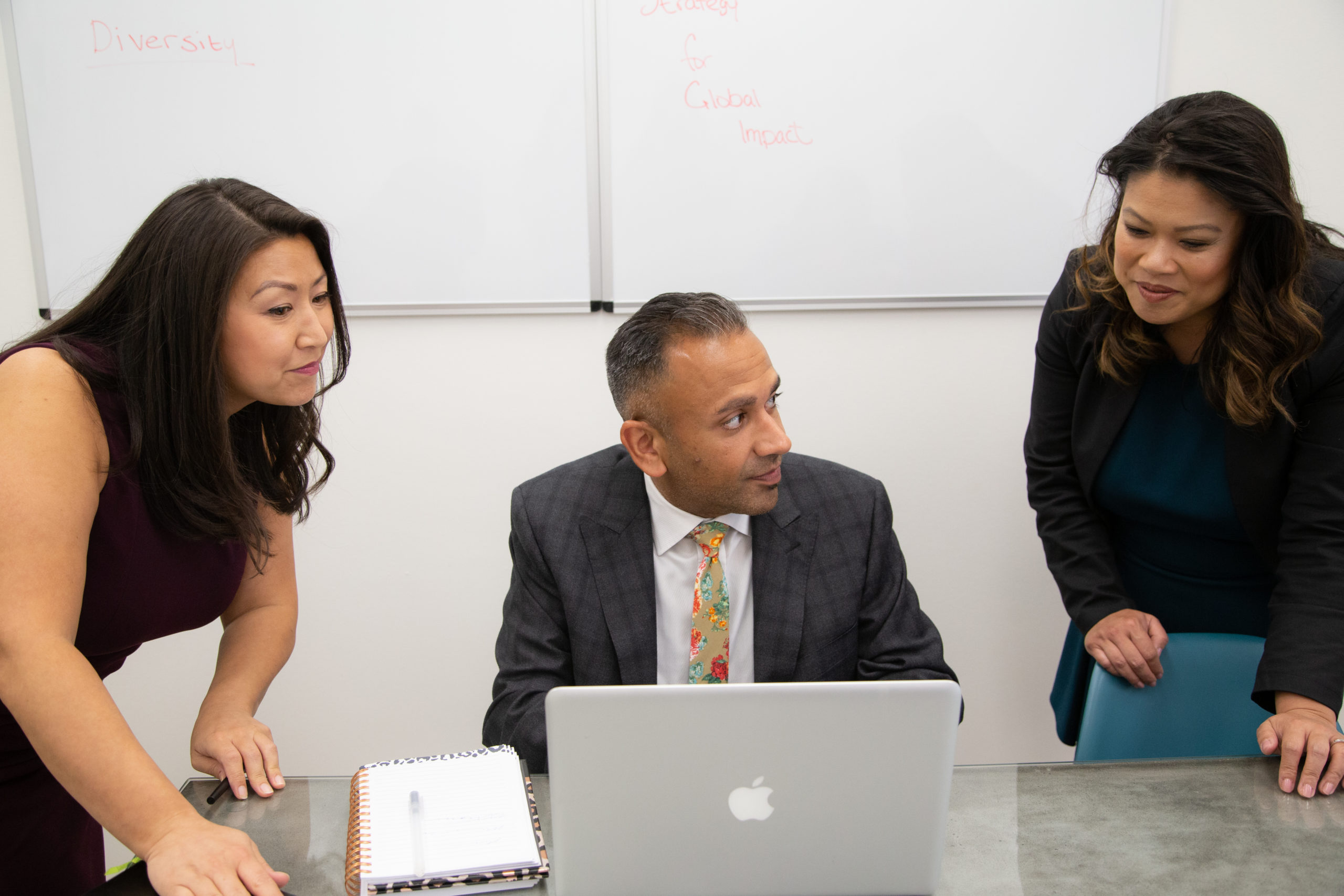 Diverse team members viewing a laptop screen